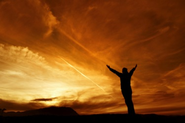 Giving thanks: Man standing with arms outstretched in thanks