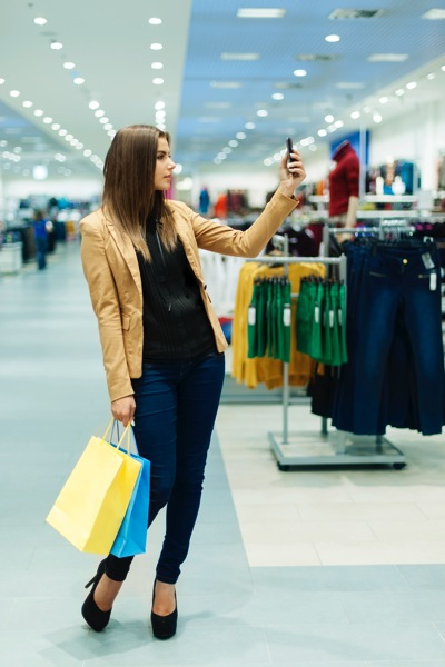 Will e-commerce kill retail? Woman shopping in store with her phone