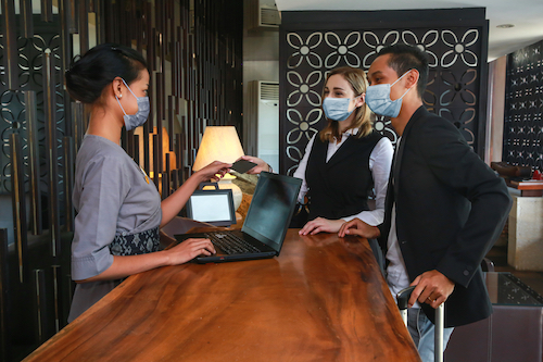 Four questions your business must ask: Customers wearing masks checking into hotel